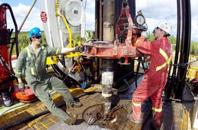 Roughnecks work on the drilling floor of Precision Drilling rig # 521.