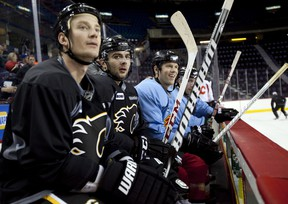 Calgary Flames, left to right, Jay Bouwmeester, Mark Giordano, and Brad Winchester, watch a drill during training camp in Calgary, Alta., Monday, Jan. 14, 2013.THE CANADIAN PRESS/Jeff McIntosh
