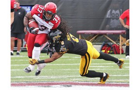 Calgary Stampeders running back Hugh Charles chugs up the field as Hamilton's Rico Murray makes the tackle during Saturday's game in the Steel City.