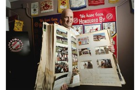 Rick Kuzyk peruses some of the scrapbooks from 50 years of the Kinsmen Club of Stampede City on Friday after the club announced a donation of $1.31 million to 11 different Calgary charities.