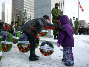 Riley Faschoway, 13, and his three-year-old cousin Emryss Agren laid a wreath for their great grandfather Calgary Higlander Ken Noonan at the base of the cenotaph as an honour guard stands in the background. Reader is glad that this year members of the honour guard dressed warmly at the Central Memorial Park monument during the Remembrance Day service.