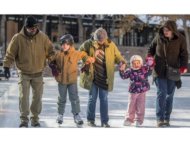 First time skaters, Duncan Harrison, 9, second from left, and his sister Ketta, 5, second from right, from Seattle, Washington, are guided by their dad Neil, left, mom Michelle, right, and their Calgarian aunt Andrea Thompson, centre, at the Olympic Plaza skating rink in Calgary, on December 30, 2014.