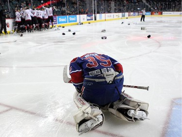 A dejected Regina Pat Canadians goalie Curtis Meger slumped on the ice as members of the Cariboo Cougars celebrated in the background after winning the Max's AAA Midget Tournament male final 2-1 in double overtime at the Scotiabank Saddledome on January 1, 2015.