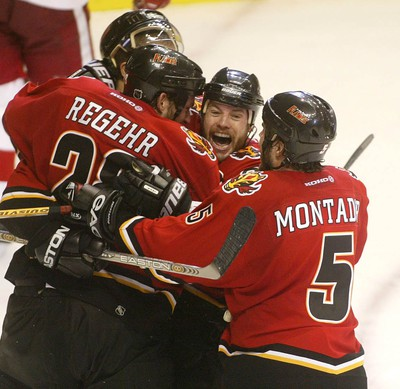Martin Gelinas celebrates his series winner against the Detroit Red Wings in the 2004 Stanley Cup playoffs with a pile of teammates, including Robyn Regehr and Steve Montador.