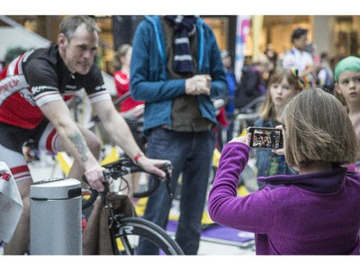 Lily Hunter, right, takes a video of her father, Simon Hunter, left, during the CANSuffer to Conquer event, in which participants ride for up to 24 consecutive hours to raise money for the fight against cancer at the Southcentre Mall in Calgary, on February 28, 2015.