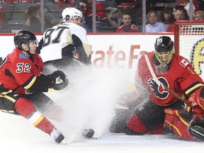Pittsburgh Penguin captain Sidney Crosby looks back as his shot goes past Calgary Flames netminder Jonas Hiller and defender Paul Byron during the second period at the Saddledome Friday February 6, 2015.