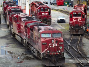 A Canadian Pacific Rail maintenance worker climbs onto a locomotive at the company's Port Coquitlam yard east of Vancouver, B.C., on May 23, 2012.