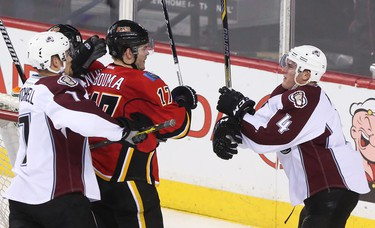 Calgary Flames centre Lance Bouma, centre, engages with Colorado Avalanche defenceman Tyson Barrie at the Scotiabank Saddledome in Calgary on Monday, March 23, 2015. The Calgary Flames lead the Colorado Avalanche, 2-1, at the end of the second period in regular season NHL play.