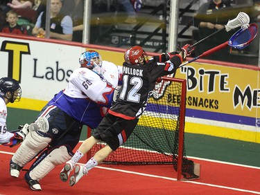 The Calgary Roughneck Sean Pollock, right, sends a leaping shot towards Toronto Rock goaltender Nick Rose at the Scotiabank Saddledome in Calgary on Saturday, March 28, 2015. The Calgary Roughnecks tied Toronto Rock, 5-5, at the half in regular season National Lacrosse League play.