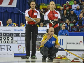 Team Canada's John Morris, left, and Pat Simmons, who took over as skip in a dramatic team switch earlier in the day, watch as Team Alberta skip Kevin Koe directs the sweepers in the Tuesday evening draw at the Tim Hortons Brier. Morris won 6-3.