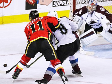 Calgary Flames centre  Mikael Backlund tangles with Colorado Avalanche defenceman Jan Hejda in front of Avalanche goaltender Semyon Varlamov during second period NHL action at the Scotiabank Saddledome Monday March 23, 2015.