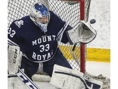 Mount Royal Cougars' goalie Dalyn Flette makes the save during CIS playoff action against the University of Calgary Dinos at Father David Bauer arena in Calgary, on March 1, 2015.
