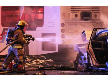 Calgary fire fighters worked to dowse the smouldering engine of an SUV which was involved in a collision with a Calgary Transit bus at the intersection of Willow Park Drive and Macleod Trail SW on March 22, 2015.