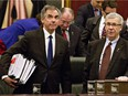 Alberta Premier Jim Prentice, left, carries the budget after Alberta Finance Minister Robin Campbell, right, delivered the 2015 budget in Edmonton, Alta., on Thursday, March 26, 2015.
