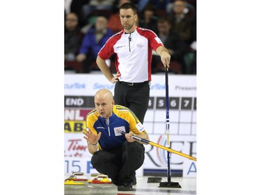 Alberta skip Kevin Koe called to his front end as Newfoundland Labrador skip Brad Gushue watched from behind during the afternoon draw at the Tim Hortons Brier at the Scotiabank Saddledome in Calgary on March 4, 2015.