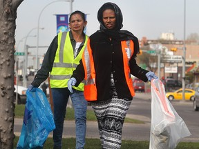 CALGARY, AB.; APRIL 22, 2015   --  Paaly Sok, left, and Tsrha Geberelsa hunt down trash on 17th Avenue SE in the Taking it to the Street Earth Day cleanup Wednesday April 22, 2015. Volunteers fanned out through the neighbourhood in the blitz sponsored by the International Avenue BRZ.  Both are from the Calgary Immigrant Education Society which sent dozens of volunteers. . (Ted Rhodes/Calgary Herald) For City Trax # 00064552A