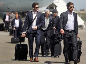 Flanked by teammates, Calgary Flames left winger Johnny Gaudreau, centre, walks to the terminal after the team returned to Calgary on Monday afternoon after losing the first two games of their series against the Anaheim Ducks.