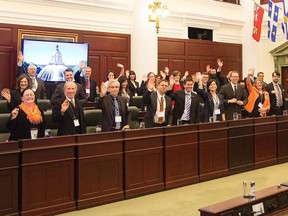 Newly-elected MLAs wave during a brief introductory meeting at the Alberta Legislature in Edmonton on Tuesday, May 12, 2015.