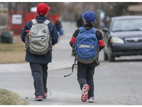 Two boys walk home from school in Calgary.