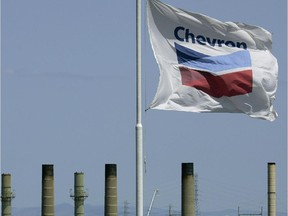 The Chevron flag flies over a refinery in California. The company is confirming a restructuring of its Canadian arm.