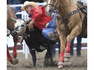 Bray Armes tackles his way to a fifth place finish during day three steer wrestling action at the 2015 Calgary Stampede, on July 5, 2015.