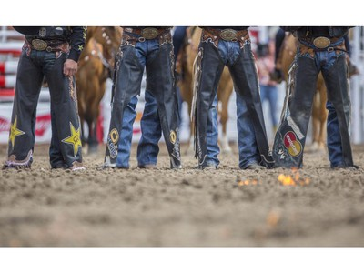 Cowboys and girls are introduced in the infield as the ground in front of them is set on fire at the onset of day three rodeo action at the 2015 Calgary Stampede, on July 5, 2015.