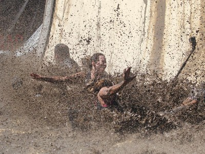 A group plashes down at the bottom of the Accelerator mud pit slide on the Rugged Maniac obstacle course Saturday July 18, 2015 at Rocky Mountain Show Jumping. Hundreds of adventurers ran, climbed and slogging through a 5 kilometre course of ropes, towers, mud and fire. The show travels across North America with it's next Canadian stop in Vancouver August 15.