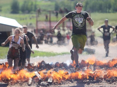Bret McIvor leaps the flames on the Pyromaniac portion of the Rugged Maniac obstacle course Saturday July 18, 2015 at Rocky Mountain Show Jumping. Hundreds of adventurers ran, climbed and slogging through a 5 kilometre course of ropes, towers, mud and fire. The show travels across North America with it's next Canadian stop in Vancouver August 15.