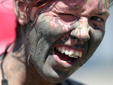 Jessica Larson with a mud splattered grin during the Rugged Maniac run Saturday July 17, 2015 at Rocky Mountain Show Jumping. Hundreds of adventurers ran, climbed and slogging through a 5 kilometre course of ropes, towers, mud and fire. The show travels across North America with it's next Canadian stop in Vancouver August 15.