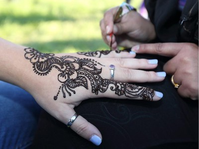Sabah Bhatti applies a traditional Pakistan henna tattoo  to one of the many multicultural booths on display at GlobalFest Saturday night.