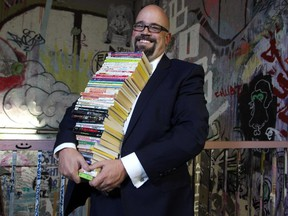 Derek Beaulieu holds a stack of titles at the Alberta College of Art and Design where he will be teaching a course based around Choose Your Own Adventure books.