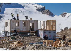 Crews work on the second story of the hut with the des Poilus Glacier in the background.