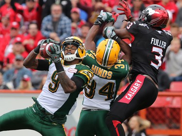 Edmonton Eskimos Patrick Watkins, left and Ryan Hinds intercept this pass for wide receiver Jeff Fuller during the first half if the Labour Day Classic action at McMahon Stadium on Monday September 7, 2015.