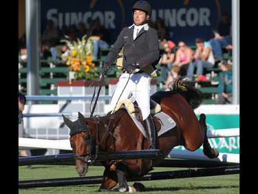 Steve Guerdat and Corbinian crash through a gate during the $210,000 Tourmaline Oil Cup at the Spruce Meadows Masters on Friday September 11, 2015. The Swiss rider and horse appeared ok.