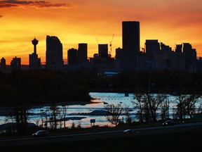 The setting sun lights  Calgary's skyline and the Bow River.