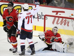 Calgary Flames defenceman Dougie Hamilton, left, and goalie Karri Ramo reacted as Washington Capitals right winger T.J. Oshie celebrates scoring the Capitals' fourth goal of the game during second period on Tuesday. Hamilton was tossed aside by a charging Oshie on the play, who scored to chase Ramo from the crease in a 6-2 Caps triumph.