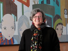 In this 2011 file photo Cheri Macaulay stands next to one of the many murals she helped intiate in her neighbourhood of Brentwood.
