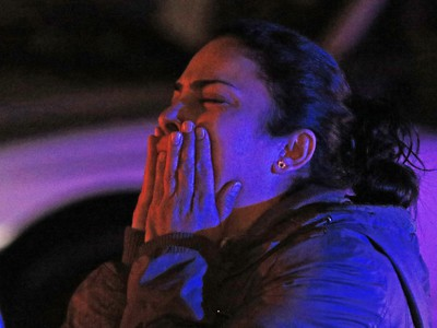 A distraught woman watches as police deal with a fatal shooting in a strip mall at 20th avenue and 52nd street S.E. on Saturday night November 14, 2015.