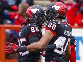 Calgary Stampeders' Joe West, left, celebrates his touchdown with teammate Eric Rogers during first half CFL football action against the Saskatchewan Roughriders in Calgary on Saturday.