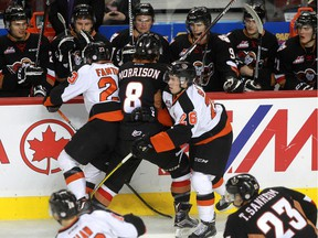 Medicine Hat Tigers Caleb Fantillo, 23,  and Cole Sanford, 26, take Hitmen's Loch Morrison out of the play in front of Calgary's bench during Saturday's game. The Hitmen are now on break until a Dec. 27 contest against the Kootenay Ice.