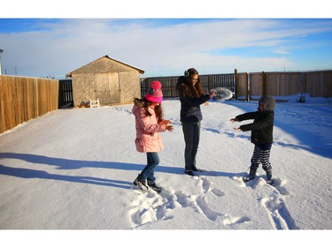 Syrian refugees Mira, 9, left, Jana,14, and Faisal, 6,  play in the snow outside their new home in Calgary.