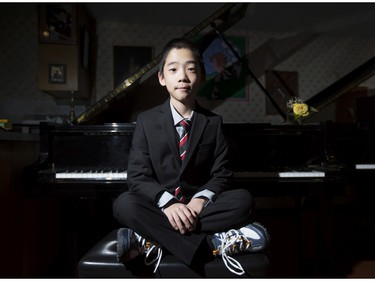 Kevin Chen, a nine year-old piano prodigy, poses for a photo at a piano with his suit and sneakers in Calgary, on February 3, 2015.
