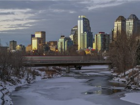 A sunset view of the Calgary downtown skyline, as the C-train crosses a bridge over the Elbow River, in Calgary, on January 7, 2015.