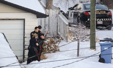 Calgary Police surround a home near where a Calgary Transit bus was hit by gunfire at 10 St. and 78 Ave. NW.
