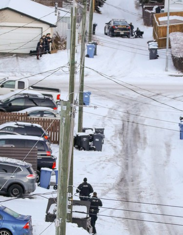 Calgary Police move in to contain a home near where a Calgary Transit bus was hit by gunfire at 10 St. and 78 Ave. NW.
