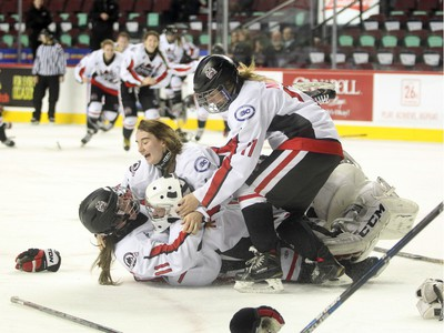 Northern Capitals players, from left to right, Sage Desjardins, Taylor Beck and Marissa Nichol mobbed goalie Kelsey Roberts after they defeated toe Rocky Mountain Raiders during the Mac's AAA Midget female final at the Scotiabank Saddledome on January 1, 2016. The Capitals defeated the Raiders 5-1 to take the 2015 title.