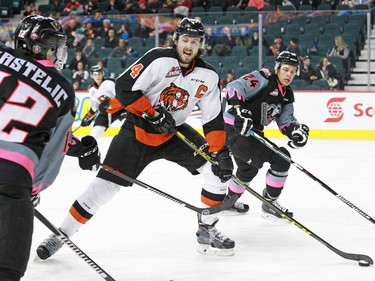 Medicine Hat Tigers captain Ty Stanton looks to pass between the The Calgary Hitmen's Mark Kastelic left and Carsen Twarynski during WHL action at the Scotiabank Saddledome on Sunday February 21, 2016.