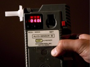FILE PHOTO: An RCMP Constable holds a breathalyzer test in Surrey, B.C., in this September 24, 2010 photo. Statistics Canada says police reported more than 90,000 impaired driving cases in 2011, about 3,000 more than in 2010.