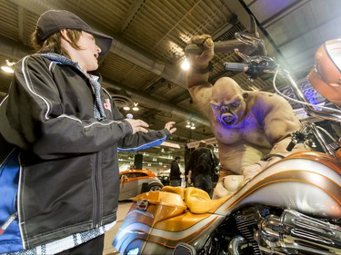 Connor McGovern, 12, checks out a monster near a Harley Davidson during the World of Wheels show at the BMO Centre in Calgary, Alta., on Saturday, Feb. 20, 2016. The popular auto-enthusiast show is in its 50th year. Lyle Aspinall/Postmedia Network
