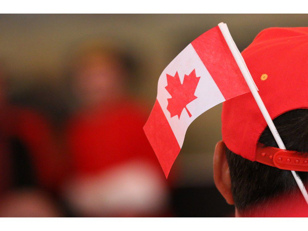 Gavin Young, Calgary Herald CALGARY, AB: JULY 01, 2015 - A new Canadian wears a flag in his had after receiving Canadian citizenship in a Canada Day ceremony at Heritage Park. (Gavin Young/Calgary Herald) (For City section story by Emma McIntosh) Trax# 00066604A // 0930 na citizenship 0930 blatchford // 1003 na citizenship